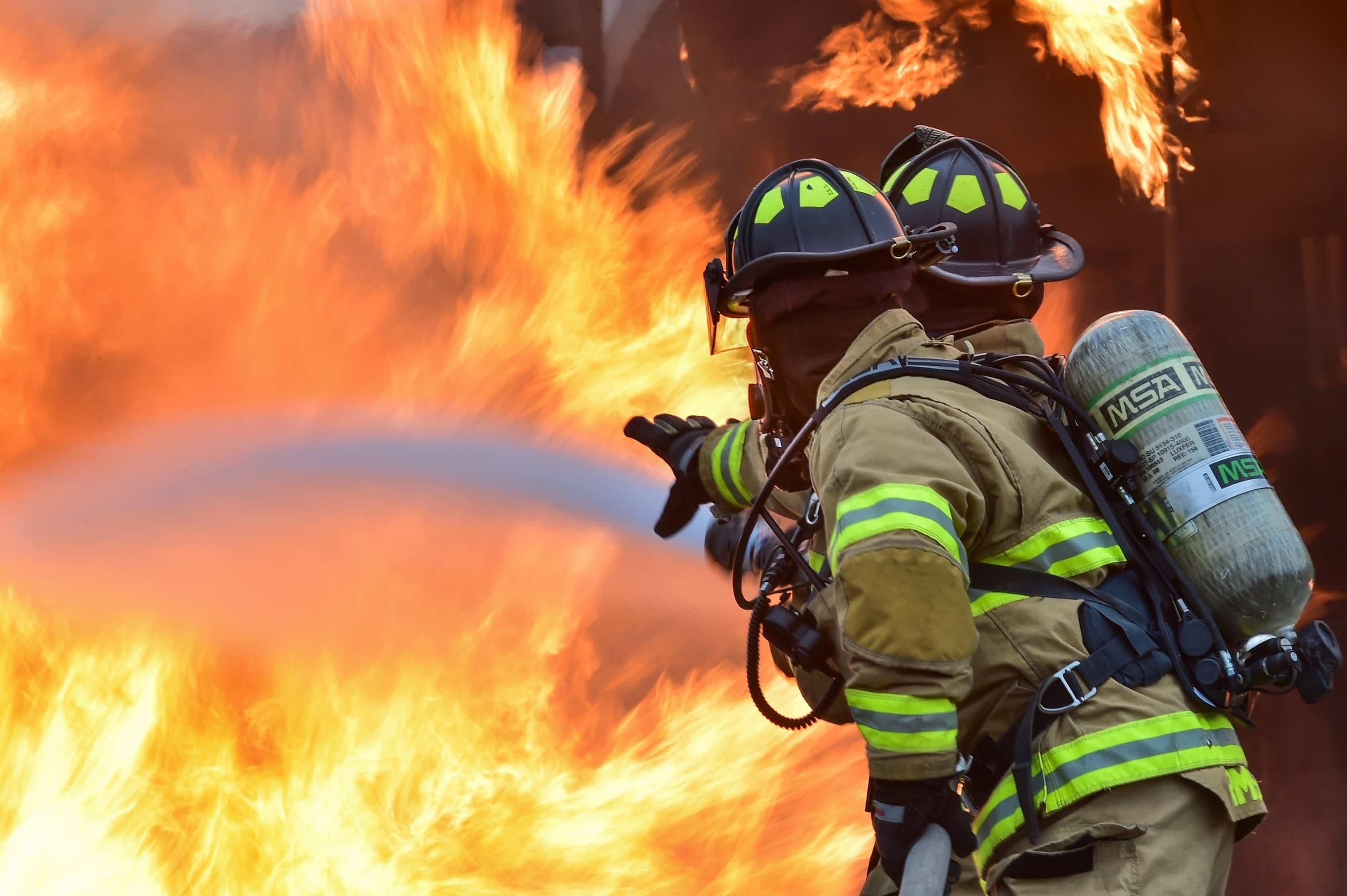 兩名消防隊員正在用水滅火