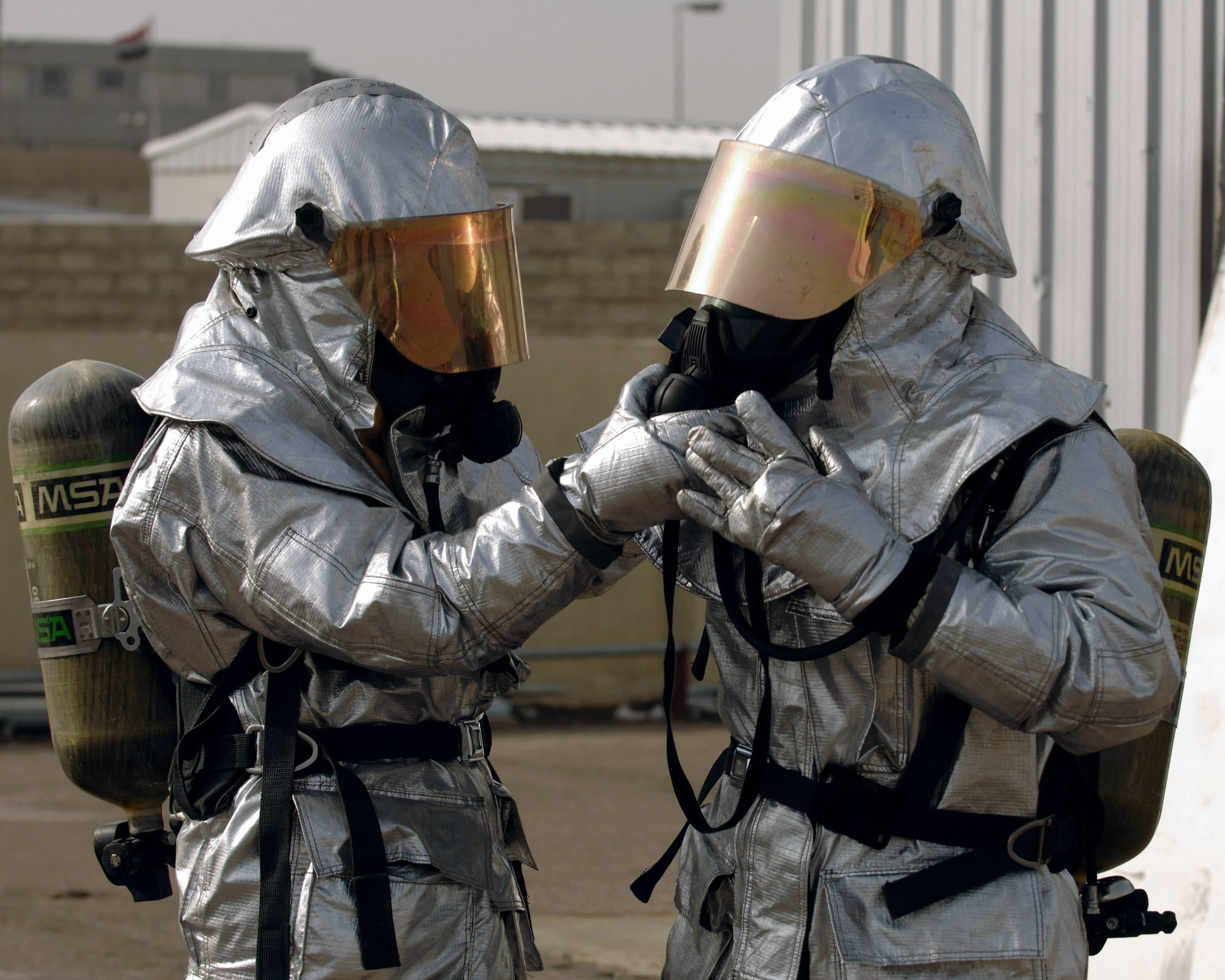 兩名消防隊員正在準備他們的發光接近服