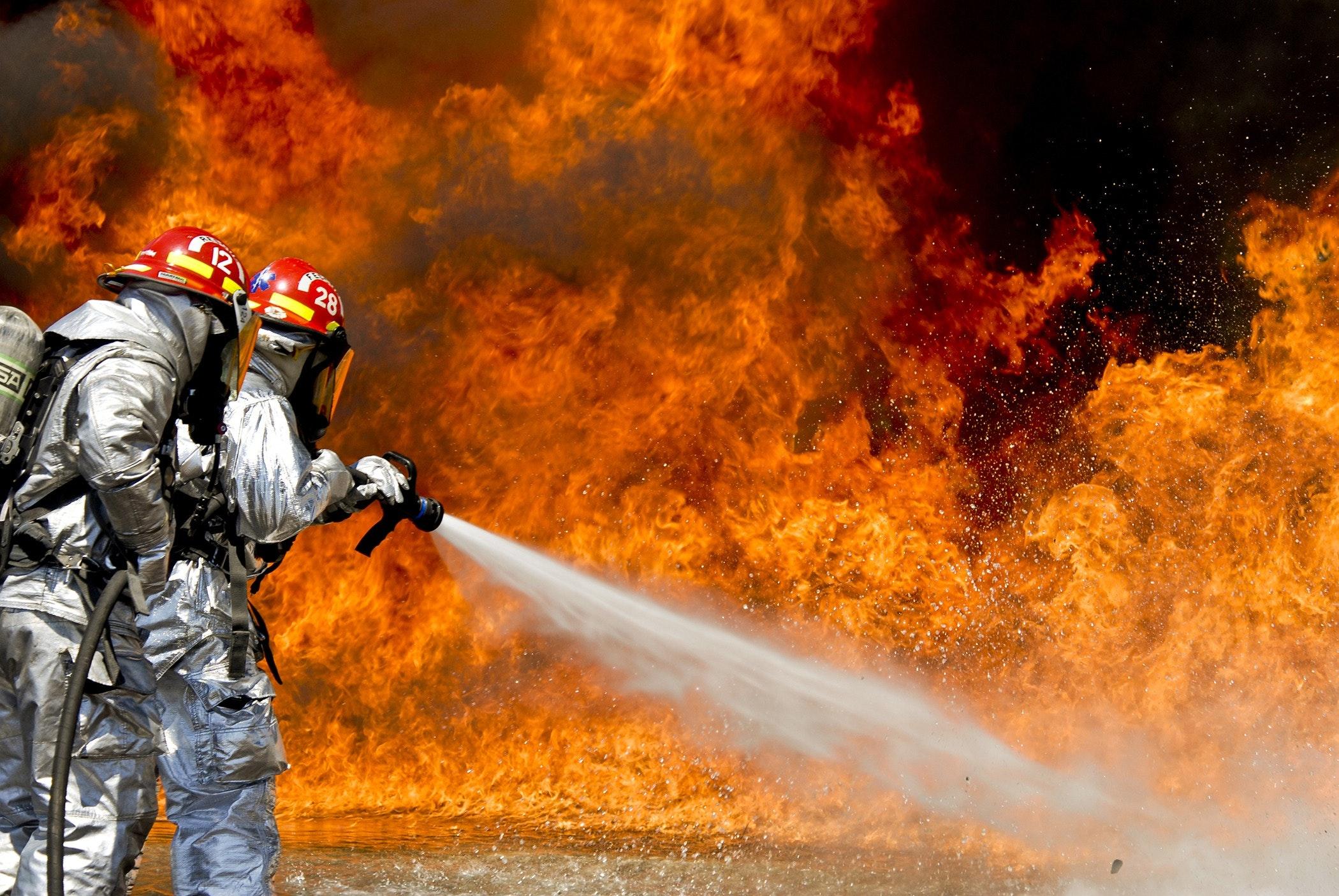 兩名身穿發光西裝的消防員正在用水滅火